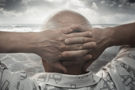 Senior man with hands behind his head looking at the sea