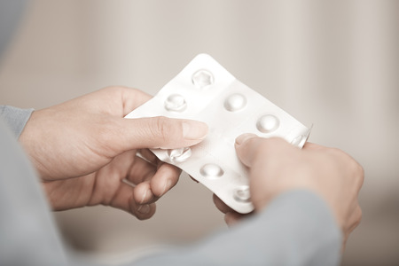 opioid: Hands of woman holding pack of medicament Stock Photo