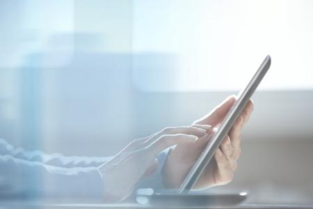 ガラスのドアの後ろにオフィスでタブレット コンピューターを使用して人間の手