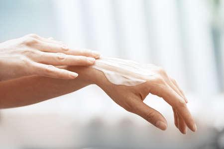 Woman applying moisturizing cream on hands Stock Photo