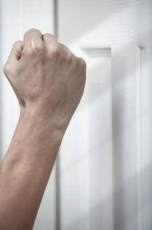 puños cerrados: La mano del hombre tocando a la puerta de madera Foto de archivo