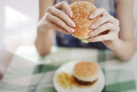 food on table: Woman holding hamburger and sitting at the table