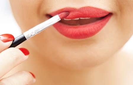l�piz labial: Mujer que aplica el l�piz labial rojo. Vista de primer plano en la cara