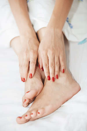 woman laying: Woman feet and hands with red nail polish