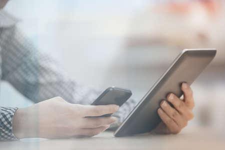 Zakenvrouw op kantoor werken met digitale tablet en smartphone beinhd het raam