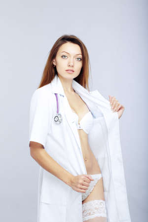 female sexuality: Sexy female doctor revealing medical uniform with stethoscope