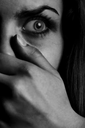 scared girl: Horror monochrome photo of the afraid woman with mouth covered by hand Stock Photo