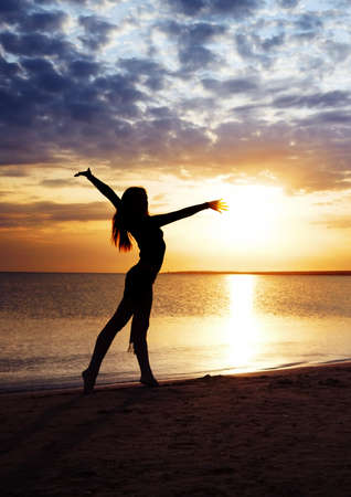 shadowgraph: Beautiful sunset and elegant lady making exercise Stock Photo