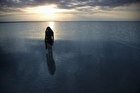 Silhouette of the single sad woman standing in the sea during sunset. Artistic colors and darkness added Stock Photo