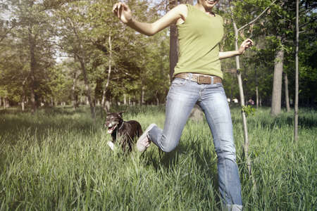 candid: Happy girl outdoors running with her dog. Horizontal photo with daylight and natural colors Stock Photo