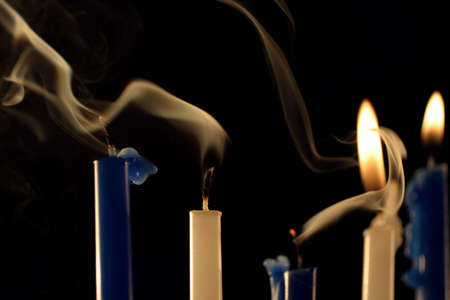 five Hanukkah candles, two are still burning, and some smoke. macro, focus on the white one, 2nd from the left.