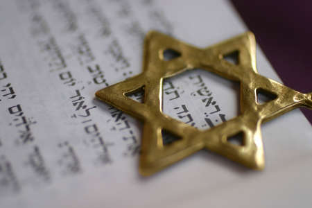 A Golden Star of David, a Jewish symbol, over the first word of the book of Genesis. Stock Photo