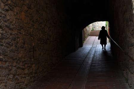 Camino de la vida - una mujer de edad de edad caminar (silueta) Foto de archivo