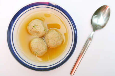 Traditional Jewish matzah ball soup, dumplings made from matzah meal - ground matzo.