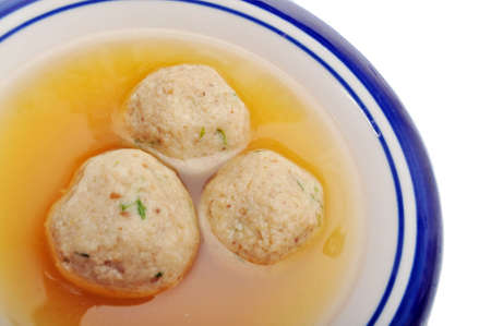 Traditional Jewish matzah ball soup, dumplings made from matzah meal - ground matzo. Over white, room for copy
