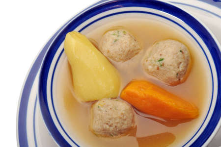 Traditional Jewish matzah ball soup, dumplings made from matzah meal - ground matzo. Over white, room for copy photo