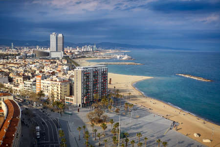 coastline: Aerial view over Barcelona coastline and beach. Shot from Montjuic cable car. Just before the rain. Stock Photo