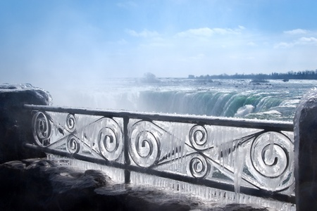 horseshoe falls: Decorative iron fence covered by thick layer of frozen mist. Niagara Falls on background.