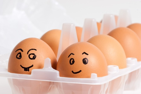 egg carton: Fresh brown eggs in a plastic container. Soft focus.