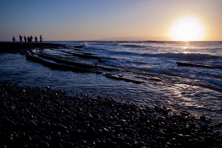 People standing at sea shore in the evening looking at sunset and throwing stones in water. Low waves. photo
