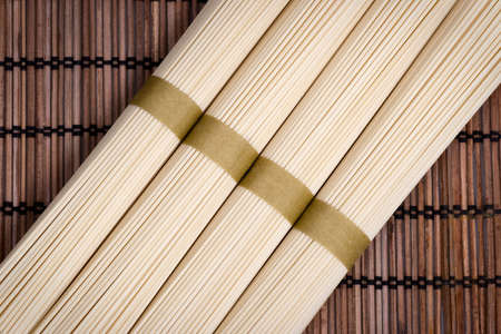 chinese noodle: Bunches of uncooked oriental noodles on a rural mat. Stock Photo