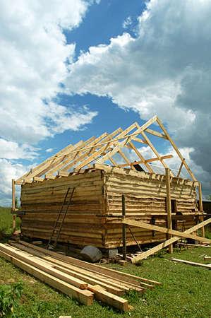 badhuis: Bouw van een badhuis uit een bar op een land site tegen de hemel met wolken Stockfoto
