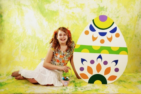 Girl and Easter eggs on color background