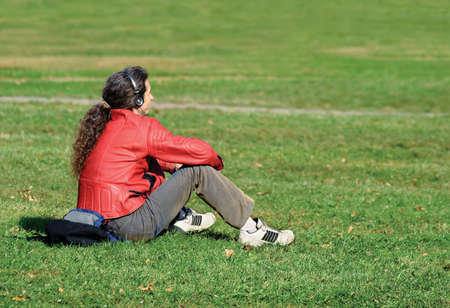 vibrat: The guy has a rest on a grass and listens to music Stock Photo