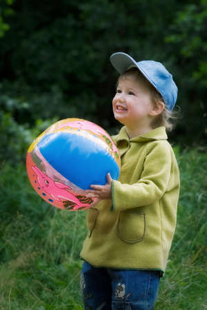 The cheerful kid with a ball in a garden photo