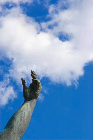 Stone hand on a background of the blue sky photo