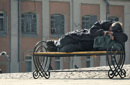 sleeps: The homeless sleeps on a bench in beams of the morning sun