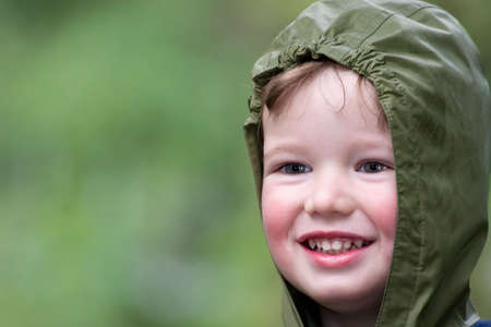 Cheerful child on walk in rainy day photo