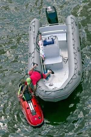 attention grabbing: The rescuer on water helps the boy to get out of water