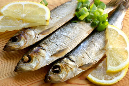 palatable: Smoked sprat-appetizing snack with a lemon and a green onions Stock Photo