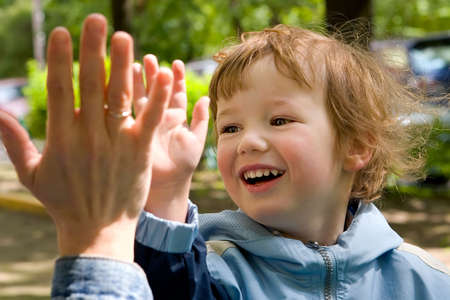 naughty child: Child cheerfully plays with gentle and kind hands of mum