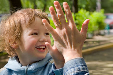 successor: Child cheerfully plays with gentle and kind hands of mum