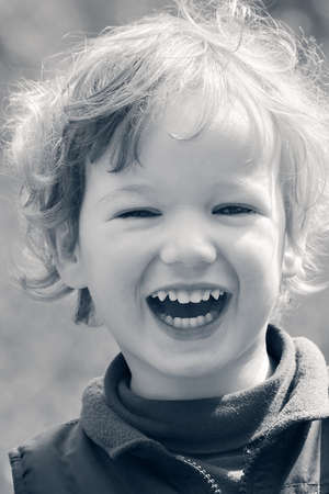 Small curly boy is cheerfully laughing and plays under the bright sun photo