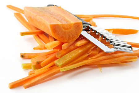 Carrots cut by slices and a knife for figured processing vegetables on a white background photo