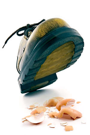 onslaught: Boot crushing an egg-metaphor of violence, pressure, wreck and force Stock Photo
