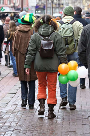 St. Patricks day -young man and girls in clothes of celebratory color easy walk on city photo