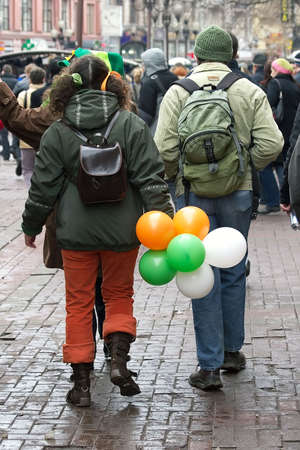 St. Patricks day -young man and girl in clothes of celebratory color easy walk on city photo