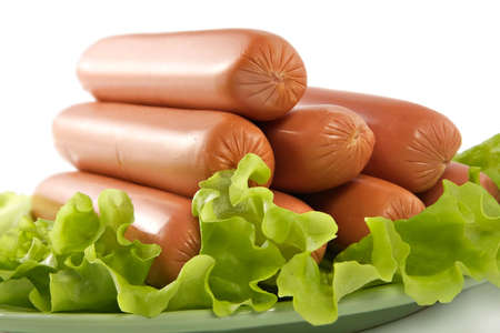 seasoned: Appetizing pork sausages seasoned by green salad-product for preparation of hot dogs Stock Photo