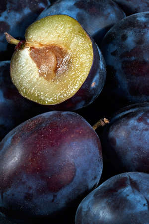 expires: Dark blue ripe fleshy plums-one from them is cut half and expires with sweet juice