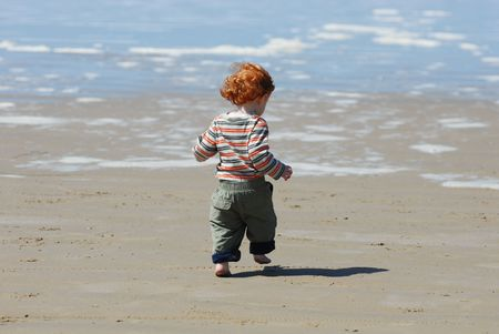 A red headed toddler runs and plays on the beach. Stock Photo