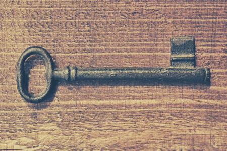 Vintage key on old wooden background photo