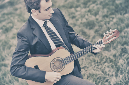 playing music: Young man playing the guitar in the grass
