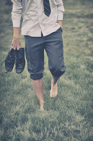 barefoot man: Man walks on grass