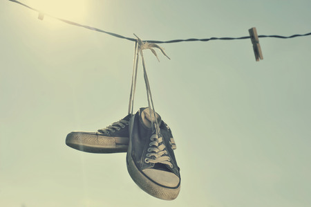clothes line: Dirty Sneakers hanging on the clothesline.