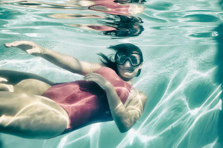 submerge: Girl swimming underwater in pool. Stock Photo