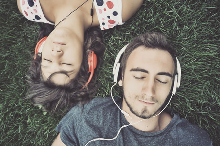 listening to people: Couple listening to music on headphones Stock Photo